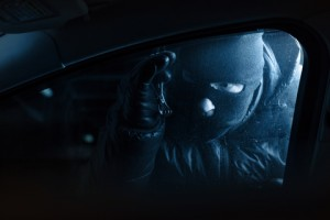 Car robber at night looking inside a car